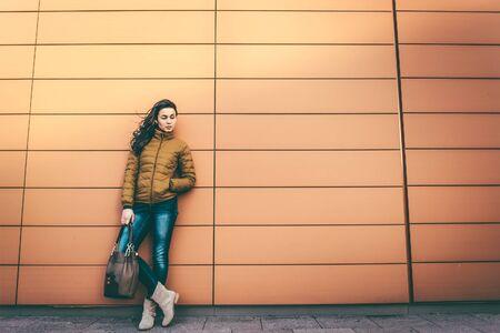 ropa de verano: Chica en la calle de la ciudad cerca de la pared con el pelo largo