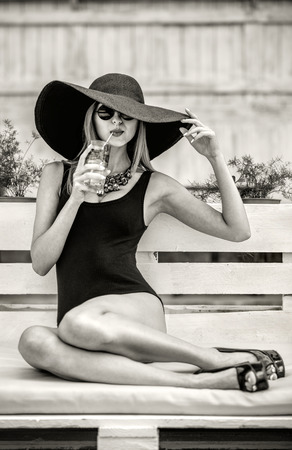 summer vacation bikini: Young pretty sexy girl drinking cold beverage outdoor in beach cafe