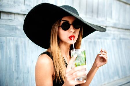 moda mujer: Joven atractiva chica linda bebe la bebida al aire fr�o en caf� de la playa