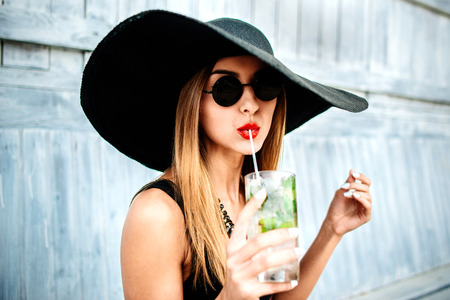 fashion sunglasses: Young pretty sexy girl drinking cold beverage outdoor in beach cafe
