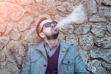 non violence: Man with beard smoking electronic sigarette outdoor