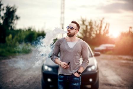 Men with beard vaping outdoor in sunglasses