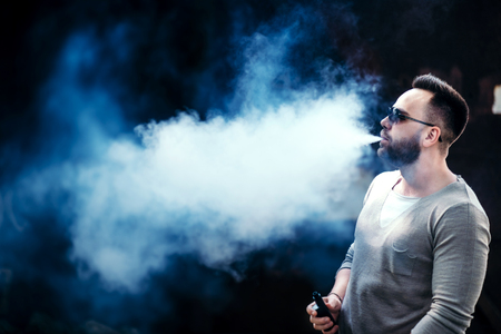 non toxic: Men with beard vaping outdoor in sunglasses