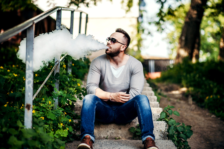 non violence: Men with beard vaping outdoor in sunglasses