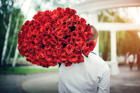 huge: Young man with big bouquet of roses outdoor