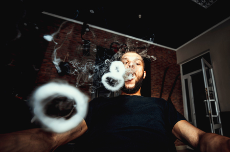 non violence: Men with beard vape and produse steam rings Stock Photo