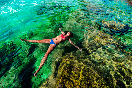 mediterranean coast: Pretty brunette girl relaxing in the water Stock Photo