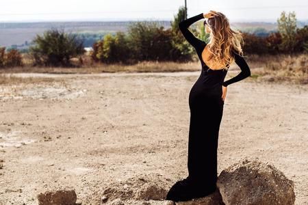 La donna in vestito lungo nero passeggiate all'aria aperta