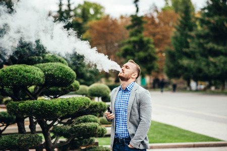 Men with beard vaping electronic cigarette outdoor Stock Photo