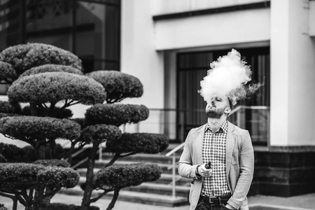 non violence: Men with beard vaping electronic cigarette outdoor Stock Photo
