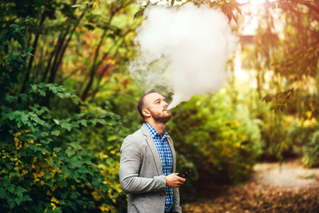 Men with beard smoking electronic cigarette outdoor