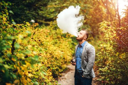 non violence: Men with beard smoking electronic cigarette outdoor
