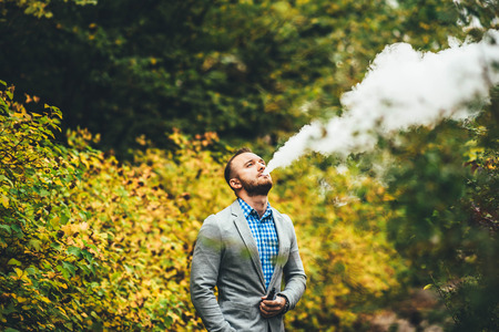 non violence: Men with beard vaping electronic cigarette outdoor Stock Photo