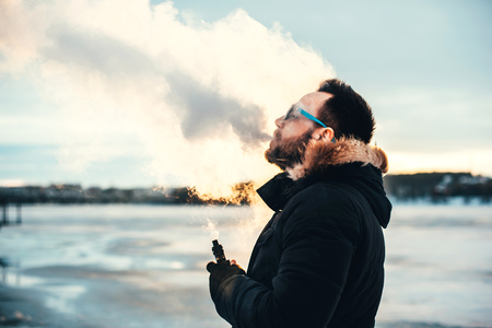 Man with beard smoke electronic cigarette outdoor