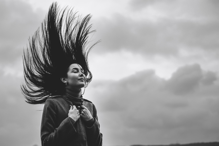 Young brunette girl outdoor with blowing up hair Banco de Imagens