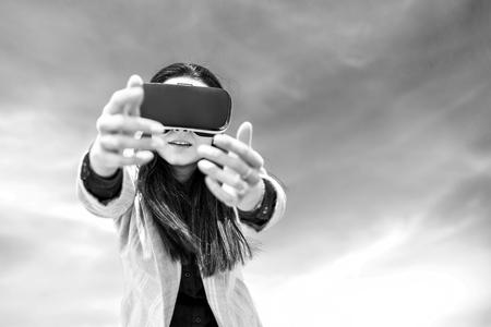 Brunette girl outdoor in VR glasses, black and white