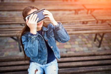 Young girl in virtual reality glasses outdoor 스톡 콘텐츠