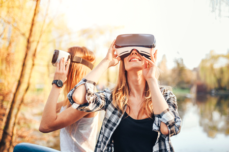 Two young girls enjoy virtual reality glasses outdoor