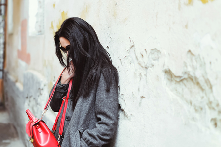 Long hair brunette girl near old wall with red backpack Stock Photo