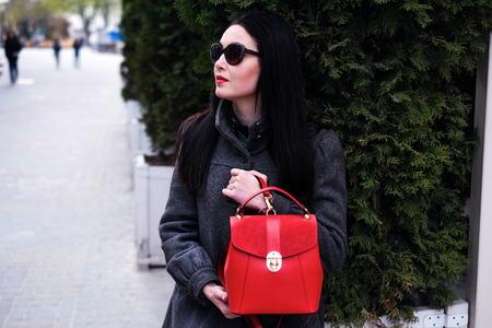 Woman on the street with red backpack in hands Stock Photo