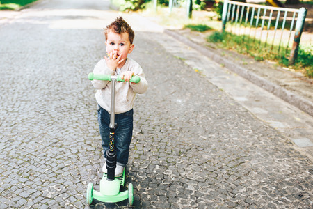 Cute little boy riding scooter outdoor on the street Stock Photo