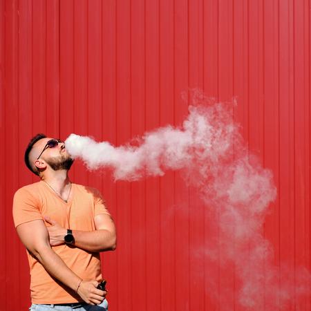 Vaper smoke electronic cigarette outdoor near wall