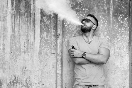 Man smoking electronic sigarette outdoor, black and white