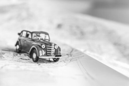 Toy retro car on the map, travel concept, black and white