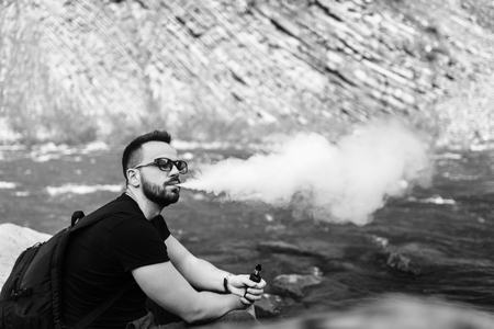 Traveler smoke electronic cigarette near mountain river, black and white Stock Photo