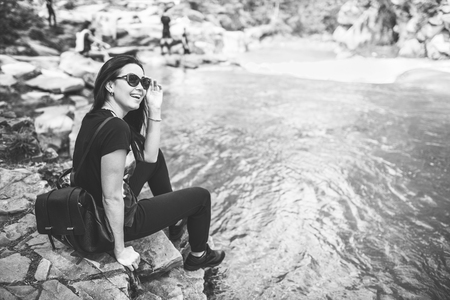 Tourist girl enjoy nature near mountain river, black and white Stock Photo