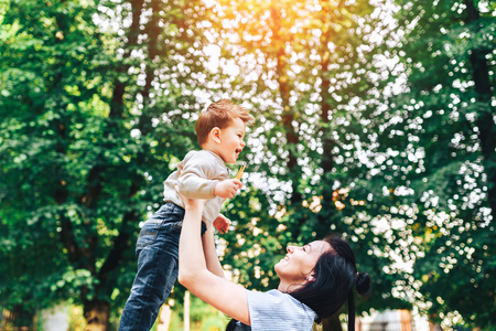 Young mother with her little son outdoor in the park Stock Photo