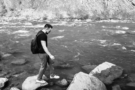 Traveler with backpack relaxing near mountain river, black and white Stock Photo