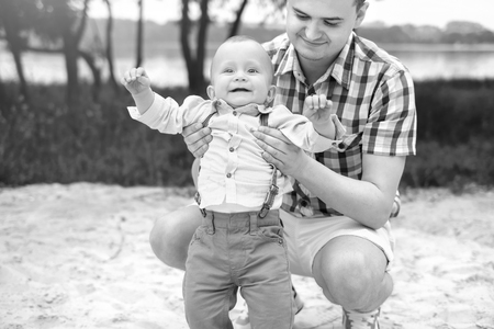 Young father with his little son have fun outdoor in the park, black and white