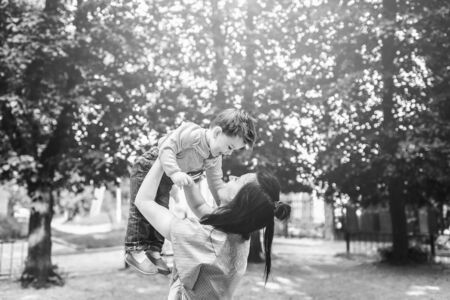 Young mother with her little son outdoor in the park, black and white