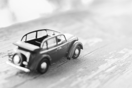 Toy car on wooden background, travel motivation, black and white