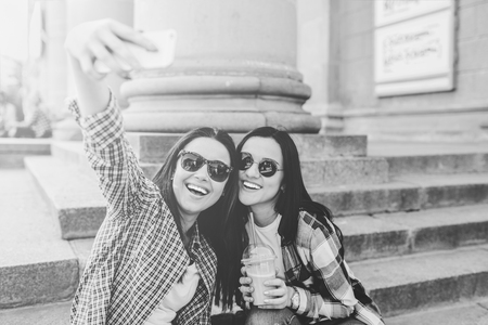 Two pretty brunette girls making selfie outdoor, black and white