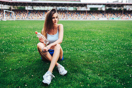 Cute sporty girl relaxing on the grass after training