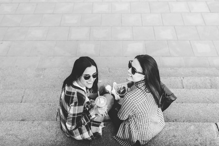Two pretty brunette girls talking and drinking coffee outdoor, black and white Stock Photo