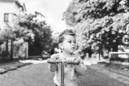 Cute little boy riding scooter outdoor on the street, black and white