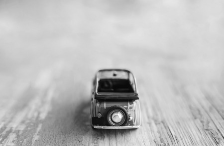Toy vintage cabrio car on wooden background, travel motivation, black and white