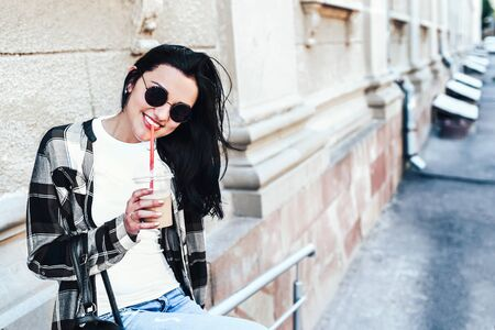 Pretty brunette girl enjoy cold coffee on the street Stock Photo