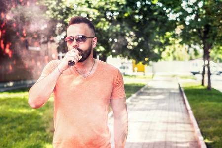 Vaper with beard with electronic cigarette outdoor