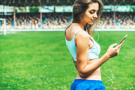 Pretty sporty girl with phone relaxing outdoor after training
