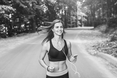 Sporty young fitness girl running and listening music in the park, black and white