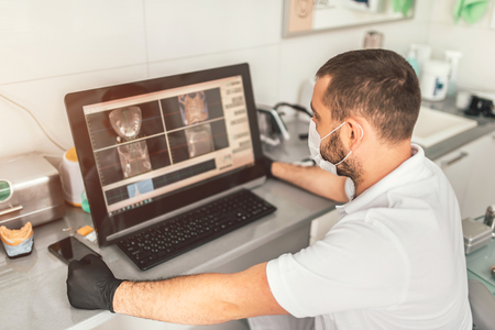 Dentist making examination of the x-ray and choosing treatment in the clinic