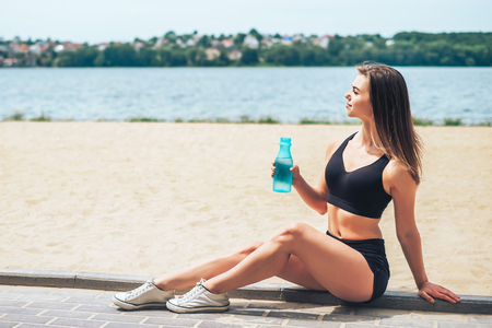 Pretty young sporty girl relaxing after outdoor training