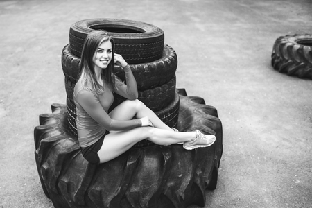 Young sporty girl workout outdoor with big tire Stock Photo