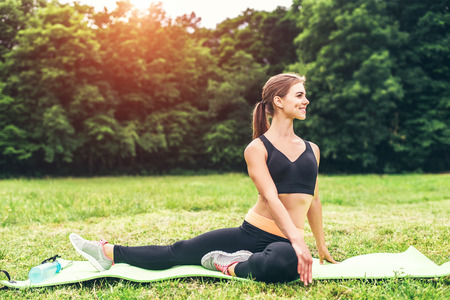 Pretty sporty girl showing stretching exercises outdoor