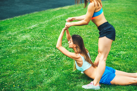 Two pretty sporty girls workout together outdoor Stock Photo