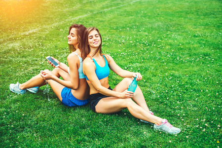 Two pretty sporty girls relaxing after workout outdoor